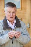 Verwirrter älterer Mann, der versucht, Tür-Schlüssel zu finden Lizenzfreies Stockbild