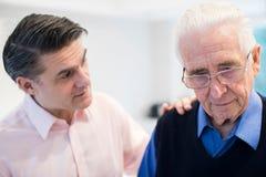 Verwirrter älterer Mann mit erwachsenem Sohn zu Hause stockbilder