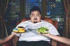 Verwirrter überladener Mann wählt Nahrung stockfotografie