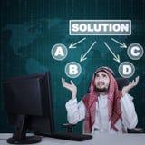 Verwirrter arabischer Geschäftsmann, der eine Lösung wählt Stockfoto