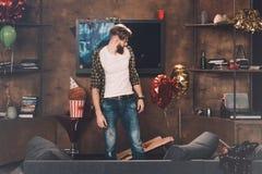 Verwirrter bärtiger junger Mann mit dem Kater, der im unordentlichen Raum steht Stockfotos