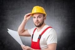 Verwirrter Bauarbeiter, der Papiere hält lizenzfreies stockfoto