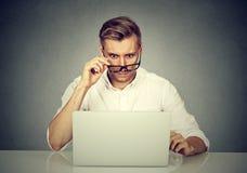 Verwirrter entsetzter Mann, der seinen Laptop betrachtet lizenzfreies stockfoto