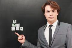 Verwirrter Geschäftsmann, der auf die Würfel an gemalt zeigt Lizenzfreie Stockfotos
