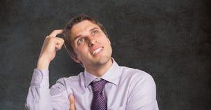 Verwirrter Geschäftsmann, der Kopf gegen Tafel verkratzt Lizenzfreie Stockfotografie