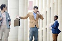 Verwirrter Geschäftsmann, der laut am Telefon spricht lizenzfreie stockfotografie