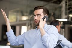 Verwirrter Geschäftsmann, der am Telefon im Büro spricht lizenzfreies stockfoto