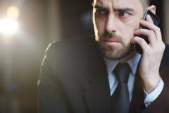 Verwirrter Geschäftsmann Speaking durch Smartphone Lizenzfreie Stockbilder