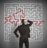 Verwirrter Geschäftsmann sucht eine Lösung zum Labyrinth Lizenzfreie Stockfotos