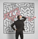 Verwirrter Geschäftsmann sucht eine Lösung zum Labyrinth Stockbilder