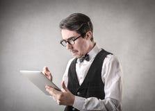 Verwirrter Geschäftsmann unter Verwendung einer Tablette stockfoto