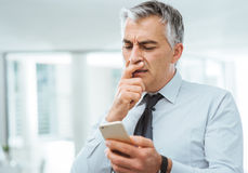 Verwirrter Geschäftsmann unter Verwendung eines intelligenten Telefons Stockfoto