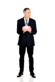 Verwirrter Geschäftsmann in voller Länge, der piggybank hält Lizenzfreie Stockbilder