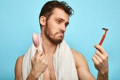 Verwirrter gezögerter enttäuschter Mann betrachtet Rasierapparat in der Hand stockfotografie