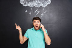 Verwirrter junger Mann, der mit Handy auf Tafelhintergrund steht Stockbilder