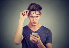 Verwirrter junger Mann, der Telefon verwendet lizenzfreie stockbilder