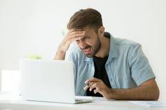 Verwirrter junger Mann frustriert durch das on-line-Problem, das lapto betrachtet stockfotografie