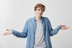 Verwirrter junger Mann mit modischer Frisur und blauen Augen trägt demin Hemd über grauem T-Shirt, Achselzuckenschultern herein Stockbilder
