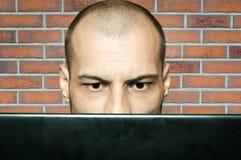 Verwirrter kahler Mann, der entlang seines Computermonitors anstarrt, während er in seinem Büro mit Wandhintergrund des roten Bac stockfoto