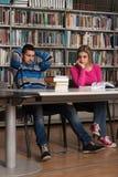Verwirrter männlicher Student Reading Many Books für Prüfung Lizenzfreies Stockbild