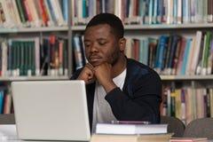 Verwirrter männlicher Student Reading Many Books für Prüfung Stockfoto