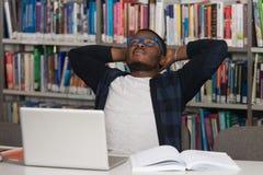 Verwirrter männlicher Student Reading Many Books für Prüfung Lizenzfreie Stockbilder