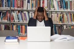 Verwirrter männlicher Student Reading Many Books für Prüfung Stockfotos