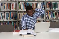 Verwirrter männlicher Student Reading Many Books für Prüfung Stockbilder