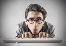 Verwirrter Mann, der auf der Tastatur schreibt Stockbilder