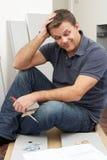 Verwirrter Mann, der Flachgehäuse-Möbel zusammenbaut Stockfotos