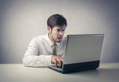 Verwirrter Mann, der am PC arbeitet lizenzfreie stockfotos