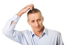 Verwirrter Mann, der seinen Kopf verkratzt Stockbild