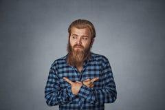 Verwirrter Mann, der in zwei verschiedene Richtungen, zögernd, Entscheidung zu treffen zeigt stockfotografie