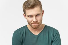 Verwirrter Mann hält Lippen gedrückt, hat frustriert Gesichtsausdruck, die Stirn runzelt Gesicht im Verdruß und ist in den Gedank lizenzfreie stockfotografie