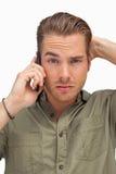 Verwirrter Mann am Telefon, das Kamera betrachtet lizenzfreie stockfotos