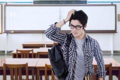 Verwirrter männlicher Student, der in der Klasse steht Stockfoto