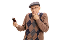 Verwirrter Senior, der eine Flasche Pillen hält Stockbild