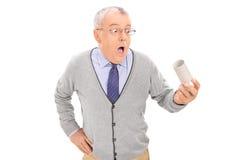 Verwirrter Senior, der eine leere Toilettenpapierrolle hält Lizenzfreies Stockbild