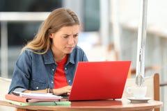 Verwirrter Student, der auf Linie mit einem Laptop sucht Lizenzfreie Stockfotografie