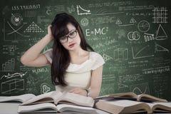Verwirrter Student, der viele Bücher liest stockfotos