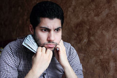 Verwirrter trauriger arabischer junger Geschäftsmann mit Dollarschein Stockbild