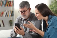 Verwirrter Vater und Tochter, die versucht, ein Telefon zu benutzen stockfotografie