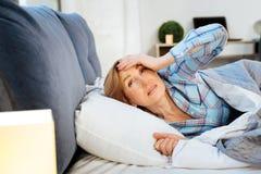 Verwirrtes Frauengefühl schläfrig beim Aufwachen früh stockfoto