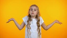 Verwirrtes Kind, das auf gelbem Hintergrund, Mangel an Ideen, fühlend zuckt unsicher stock footage