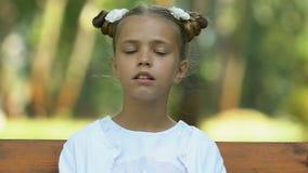 Verwirrtes kleines Mädchen, das allein auf der Bank, herum schauend, Mangel an Freunden sitzt stock video footage