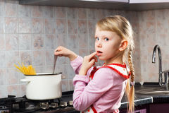 Verwirrtes Mädchen, das in der Küche kocht stockfoto