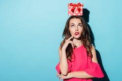 Verwirrtes Mädchen mit Geschenkbox auf ihrem Kopf, der oben schaut Lizenzfreie Stockfotografie