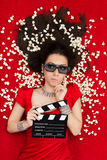 Verwirrtes Mädchen mit Gläsern des Kino-3D, Popcorn und Direktor Clapboard Stockfoto
