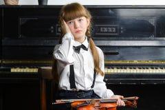 Verwirrtes oder beunruhigtes Mädchen, das ihren Kopf erfasst und eine Violine hält Stockbilder