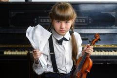 Verwirrtes oder beunruhigtes Mädchen, das ihren Kopf erfasst und eine Violine hält Stockbild
